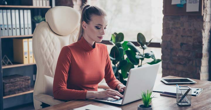 Woman in an office typing on laptop