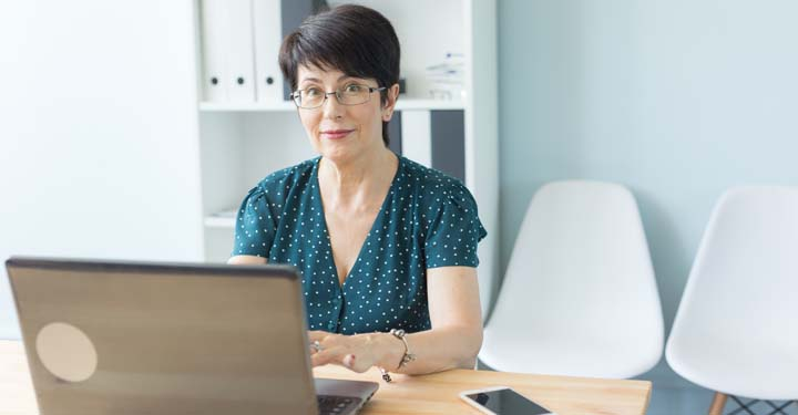 Woman wearing glasses using laptop