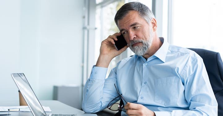Man speaking on phone while looking at laptop