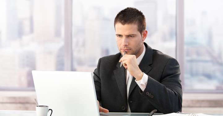 Business man with men on his chin looking intently at his laptop