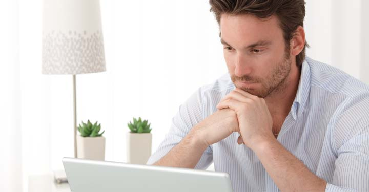 Man resting his chin on his hands as he looks intently at his laptop