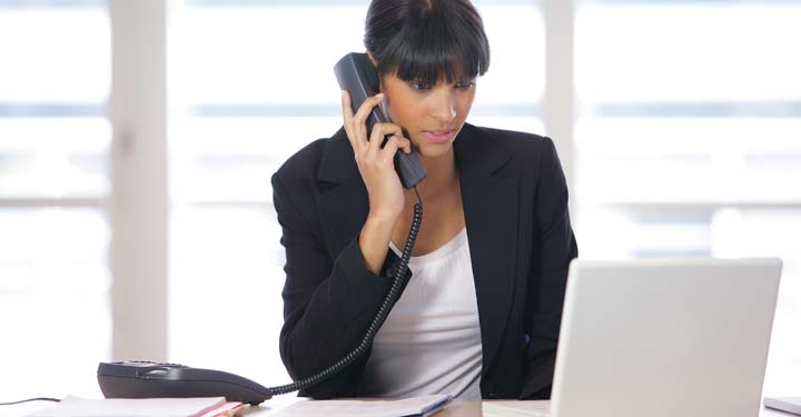 Businesswoman looking at laptop talking on telephone