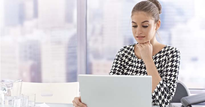 Woman resting chin on hands looking at a laptop