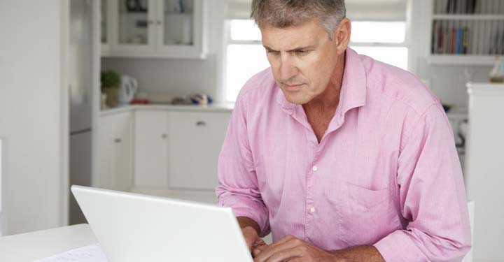 Man in pale pink button-down shirt using laptop
