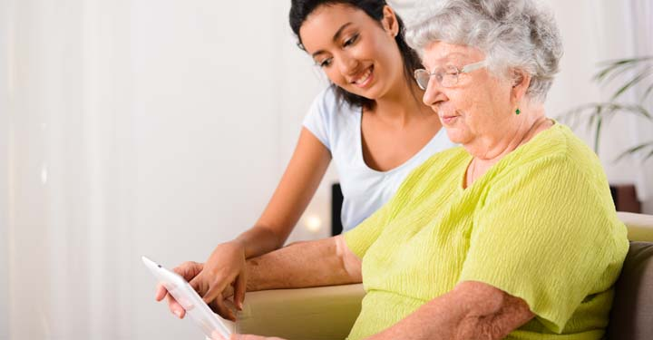 Young woman pointing to tablet that elderly woman is holding