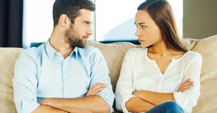 Man and woman sitting on a couch with crossed arms looking angrily at each other