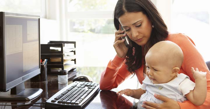 Woman talking on the phone at her computer holding a crying infant