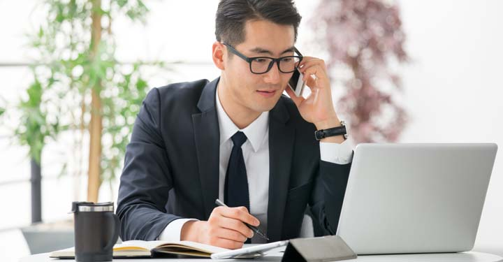 Businessman at a desk talking on the phone, looking at an open laptop, and writing in a notebook