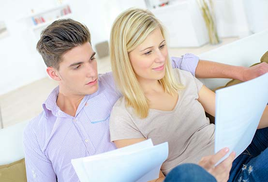 Young couple looking over documents on couch