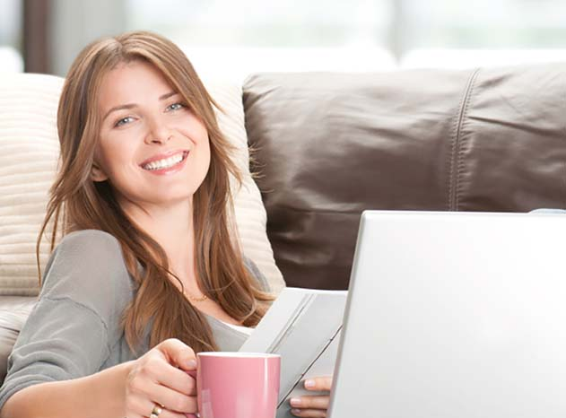 Woman smiling in front of laptop with pink mug