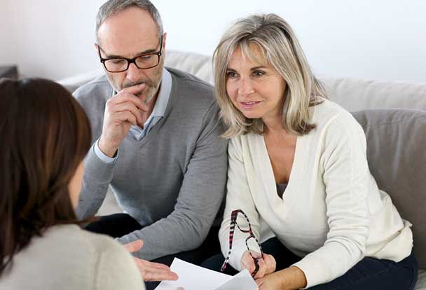 Older man in couple looking down at documents with concern while older woman holds glasses and gazes into eyes of young brunette woman gesturing towards document