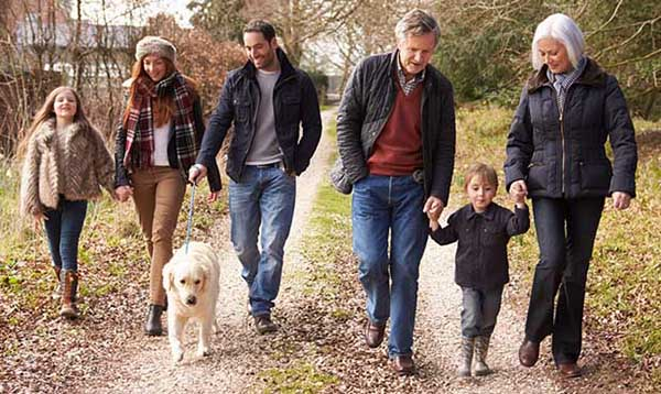 Family, including grandparents and young children, walking dog along quaint road in nature
