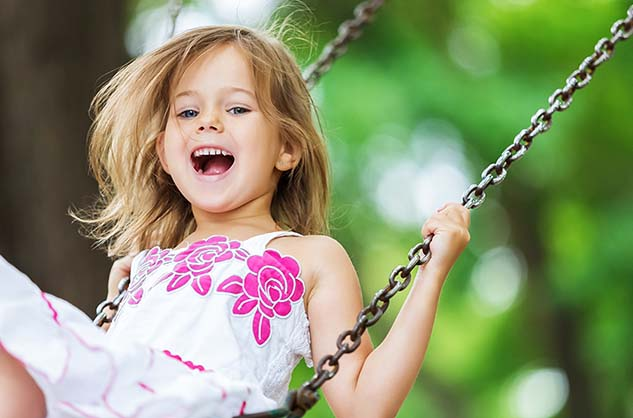 Child smiling on swing