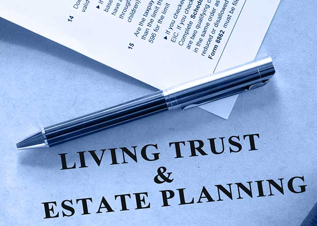 "Pen resting on document that reads ""living trust and estate planning"""