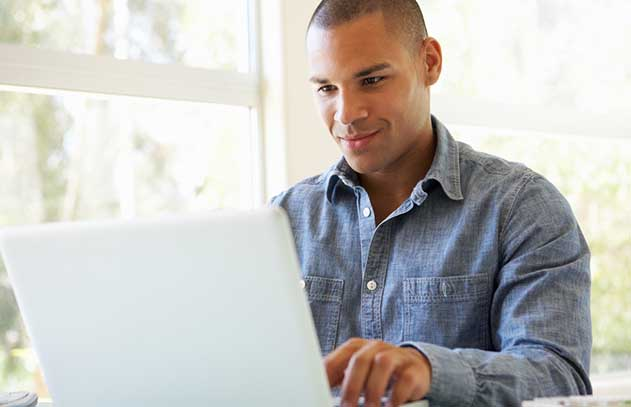 Man in button down shirt smiling at laptop