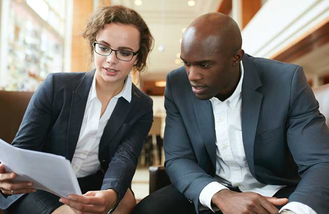 Businesswoman and businessman looking over document together