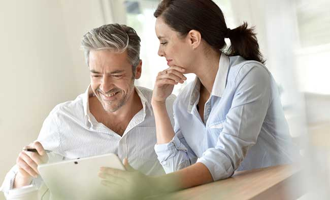 Man and woman smiling while looking at iPad in well lit room