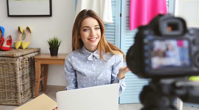 Woman smiling in front of camera and laptop