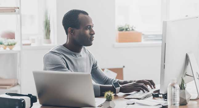 Man in light grey sweater types on desktop computer at messy desk
