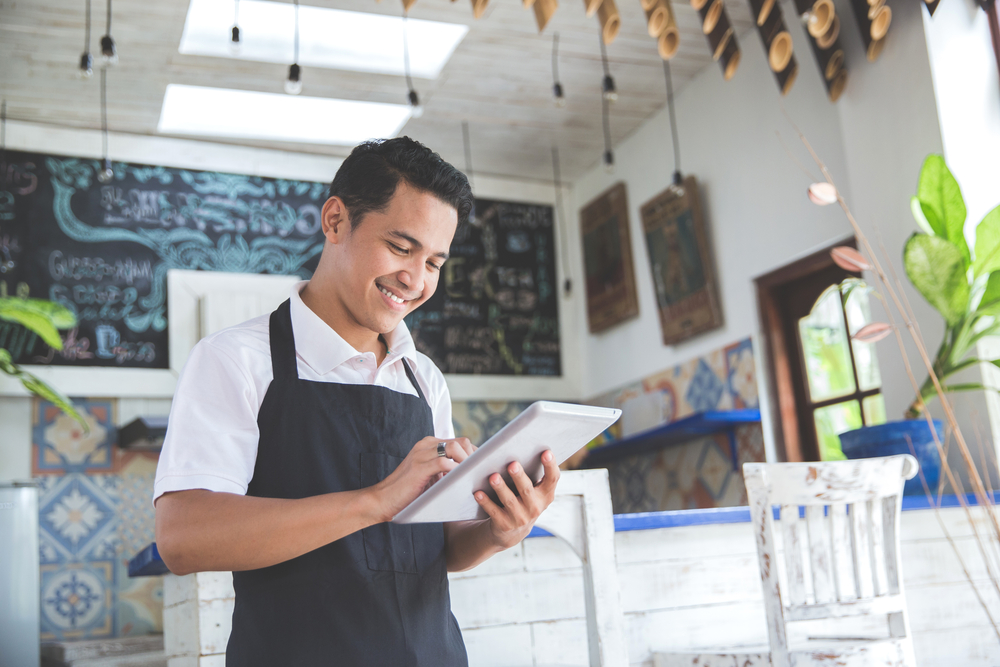 Man wearing apron in restaurant and smiling down at tablet