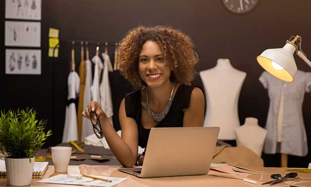 Woman smiling with laptop in front of fashion designs and mannequins