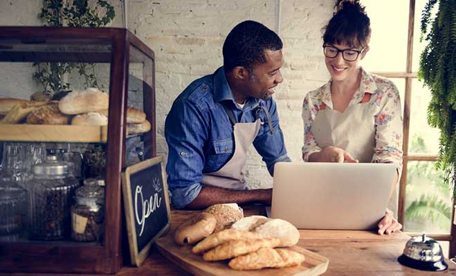 Man and woman in aprons smile at each other while looking at laptop at counter of cafe