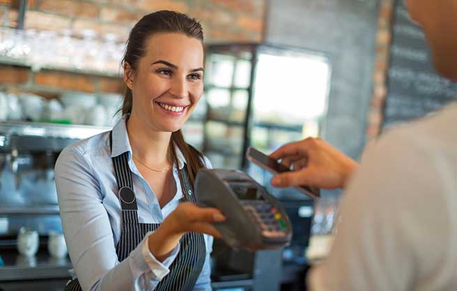 Woman in black apron holds out a credit card reader to a customer