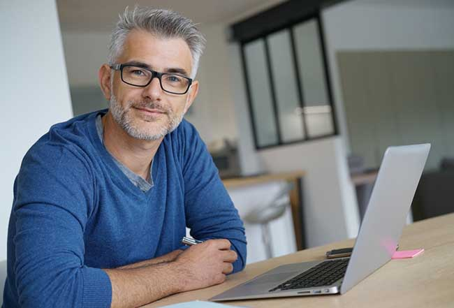 Man with silver hair and black glasses looking forward while sitting at table in front of laptop